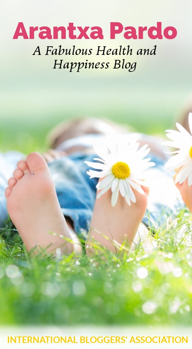 Laying in grass with daisy in toes and text overlay 'Arantxa Pardo - A Fabulous Health and Happiness Blog' by International Bloggers' Association