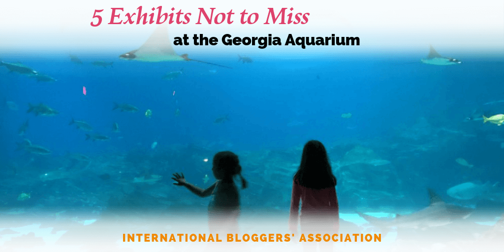 "girls standing in front of aquarium window with text overlay ""5 Exhibits Not to Miss at the Georgia Aquarium."""