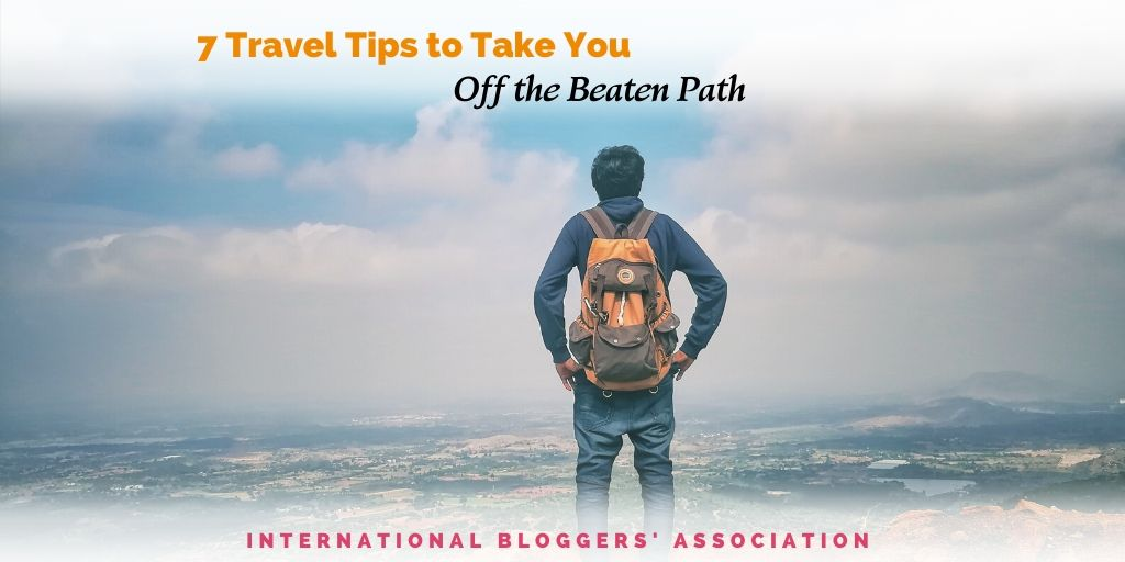 "man standing on a bluff overlooking a city with text overlay ""7 Travel Tips to Take You Off the Beaten Path"""